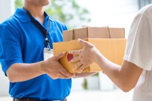 Paketbote übergibt Paket an der Haustür